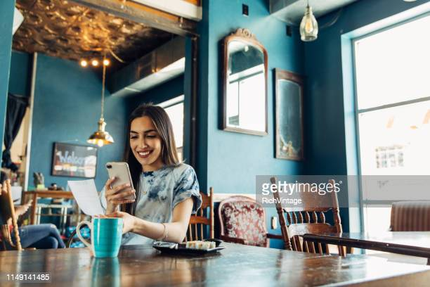 hispanic woman tracking restaurant bill - receipt stock pictures, royalty-free photos & images