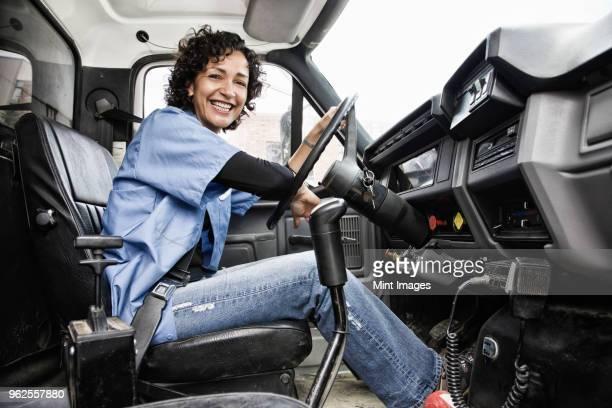 hispanic woman truck driver and company delivery truck. - camioneros fotografías e imágenes de stock