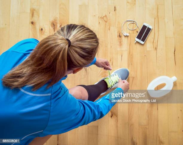 Hispanic woman tying shoelace before running