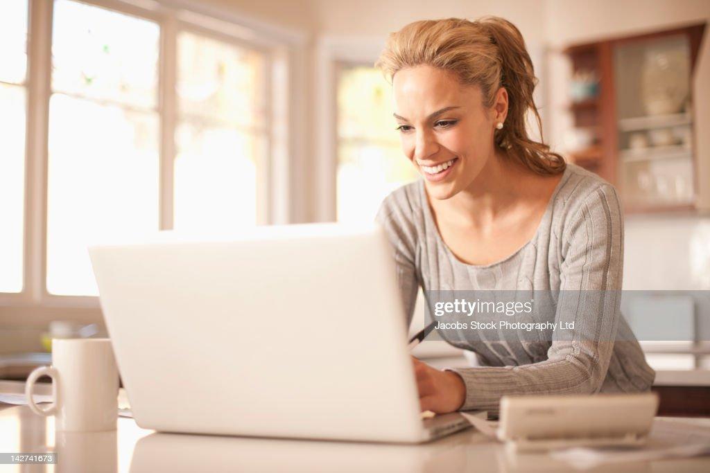 Hispanic Woman Typing On Laptop High-Res Stock Photo ...