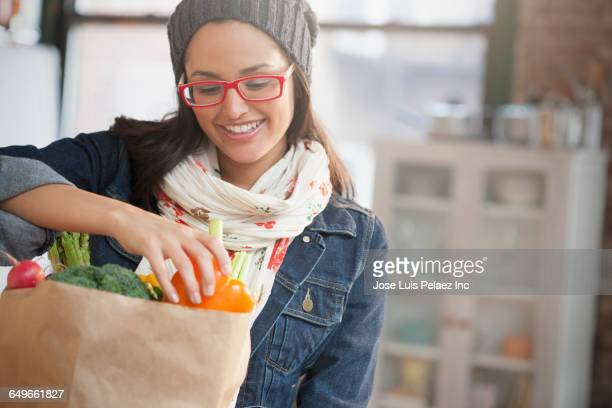 hispanic woman unpacking groceries - unpacking stock pictures, royalty-free photos & images