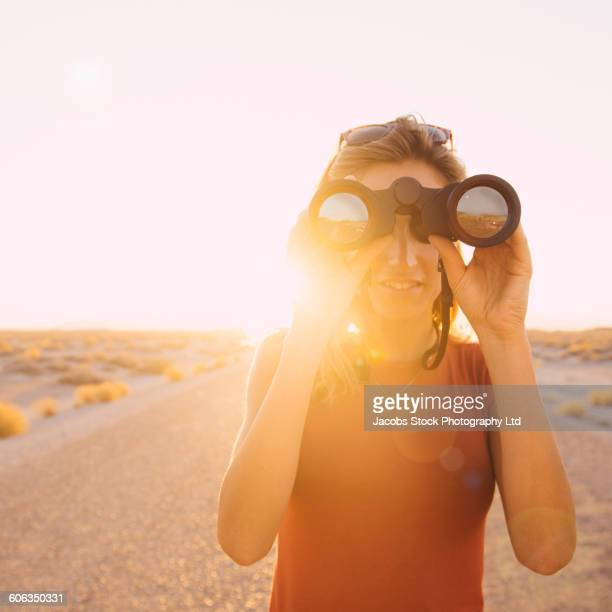 Hispanic woman using binoculars on remote road