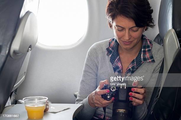 Hispanic woman using camera in airplane