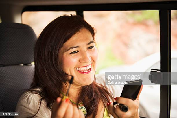 Hispanic woman using cell phone in car