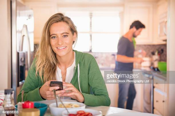 Hispanic woman using cell phone in kitchen