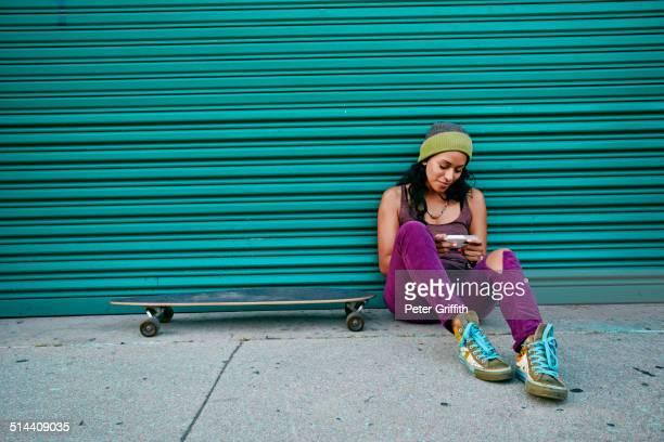 Hispanic woman using cell phone on city street