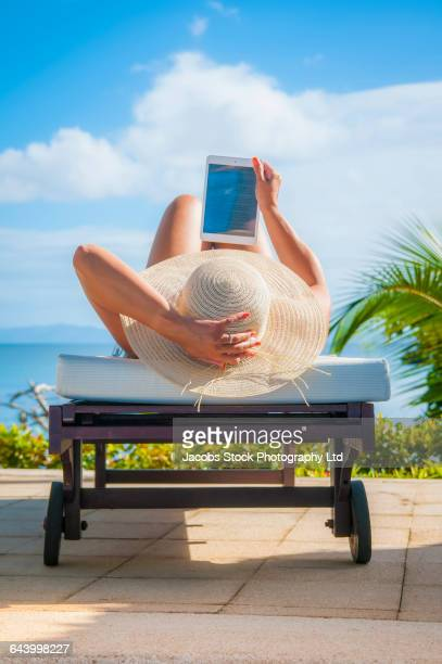 Hispanic woman using digital tablet outdoors