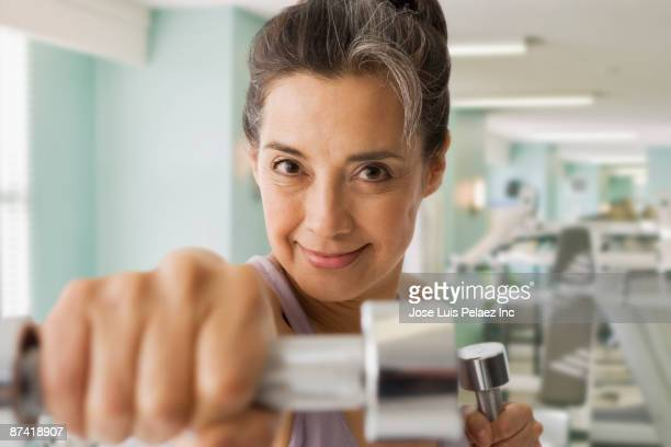 Hispanic woman using hand weights in health club