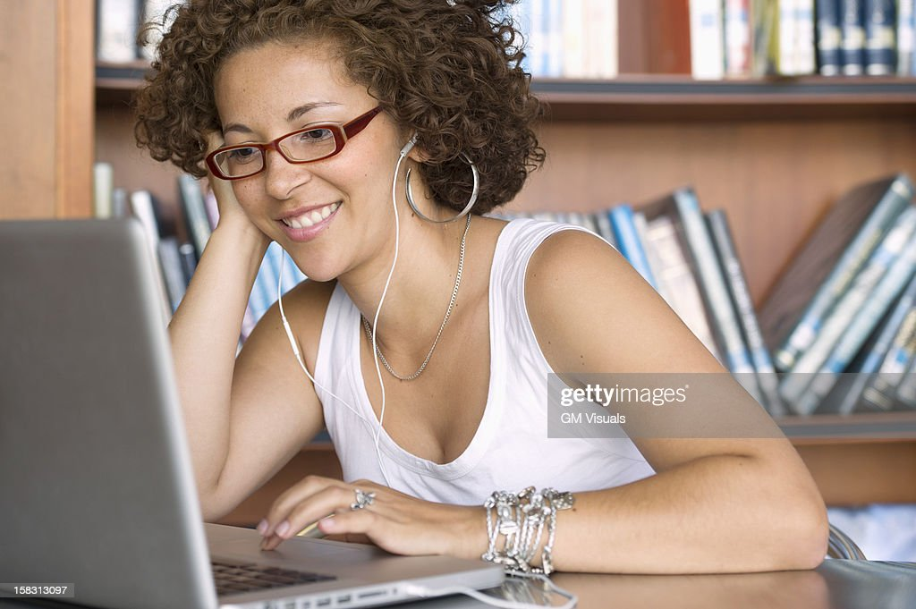 Hispanic woman using laptop in library : Stock Photo