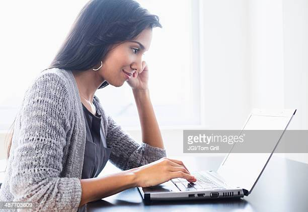 Hispanic woman using laptop on table