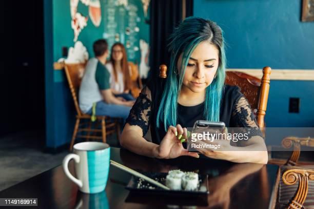 hispanic vrouw met behulp van telefoon bij de lunch - moeiteloos stockfoto's en -beelden