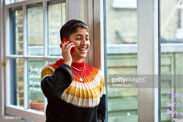 hispanic woman using smartphone by office window - beautiful woman stock pictures, royalty-free photos & images