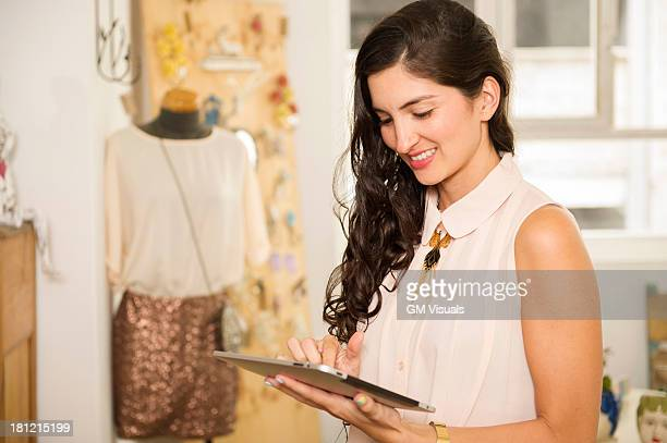 Hispanic woman using tablet computer in shop