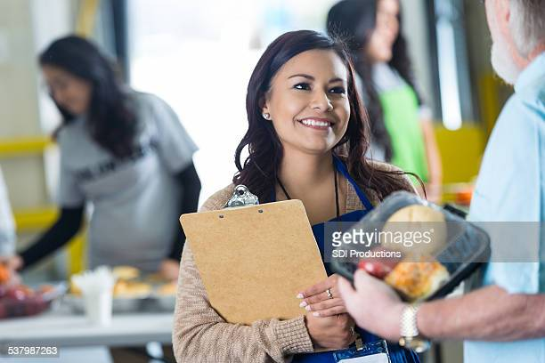 hispanic woman volunteering in food bank, serving meal to seniors - non profit organization stock pictures, royalty-free photos & images