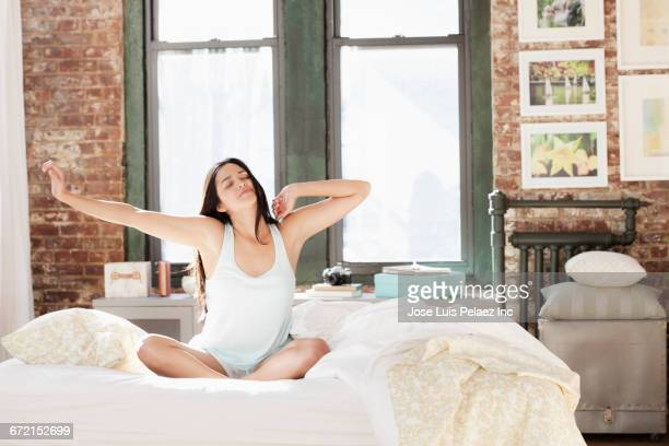 hispanic woman waking in morning and stretching arms - waking up stock pictures, royalty-free photos & images