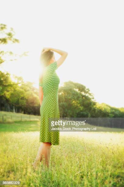 Hispanic woman walking in field