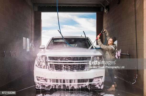 hispanic woman washing car at self-serve car wash - car wash stock photos and pictures