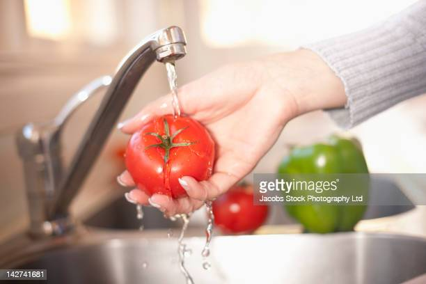 Hispanic woman washing tomato