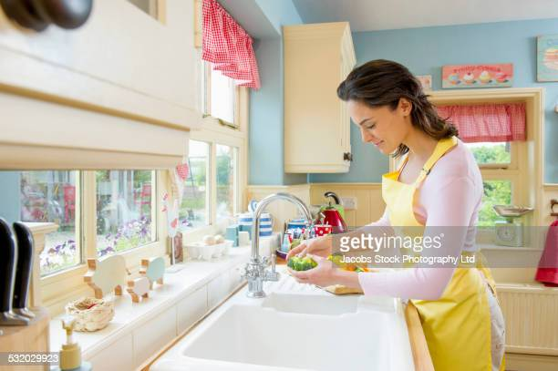 Hispanic woman washing vegetables at kitchen sink