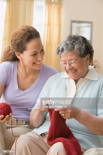 Hispanic woman watching mother knit