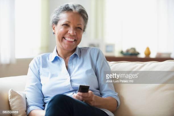 Hispanic woman watching television on sofa