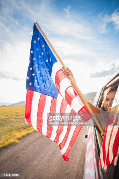 Hispanic woman waving American flag out car window
