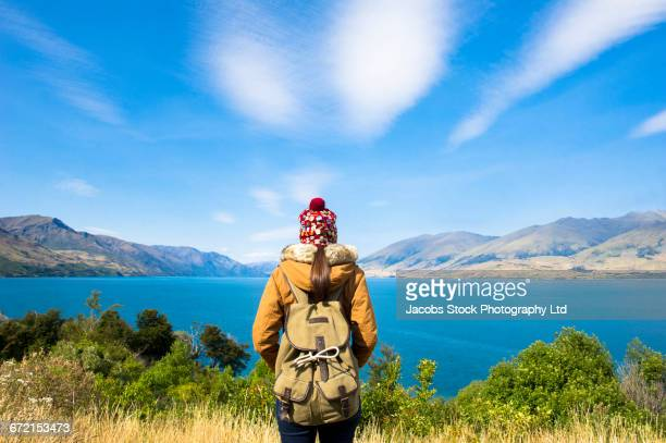 Hispanic woman wearing backpack admiring mountain lake