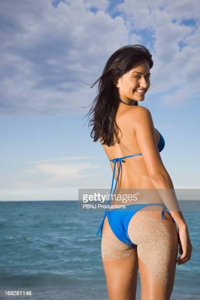 Hispanic woman wearing bikini on beach