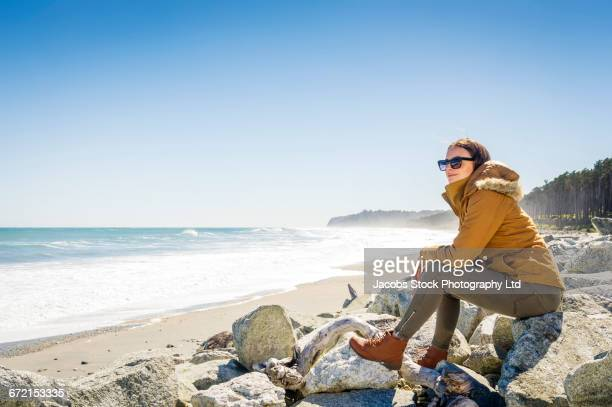 Hispanic woman wearing coat sitting on rocks at beach