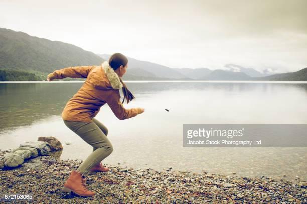 Hispanic woman wearing coat skipping rock at mountain lake