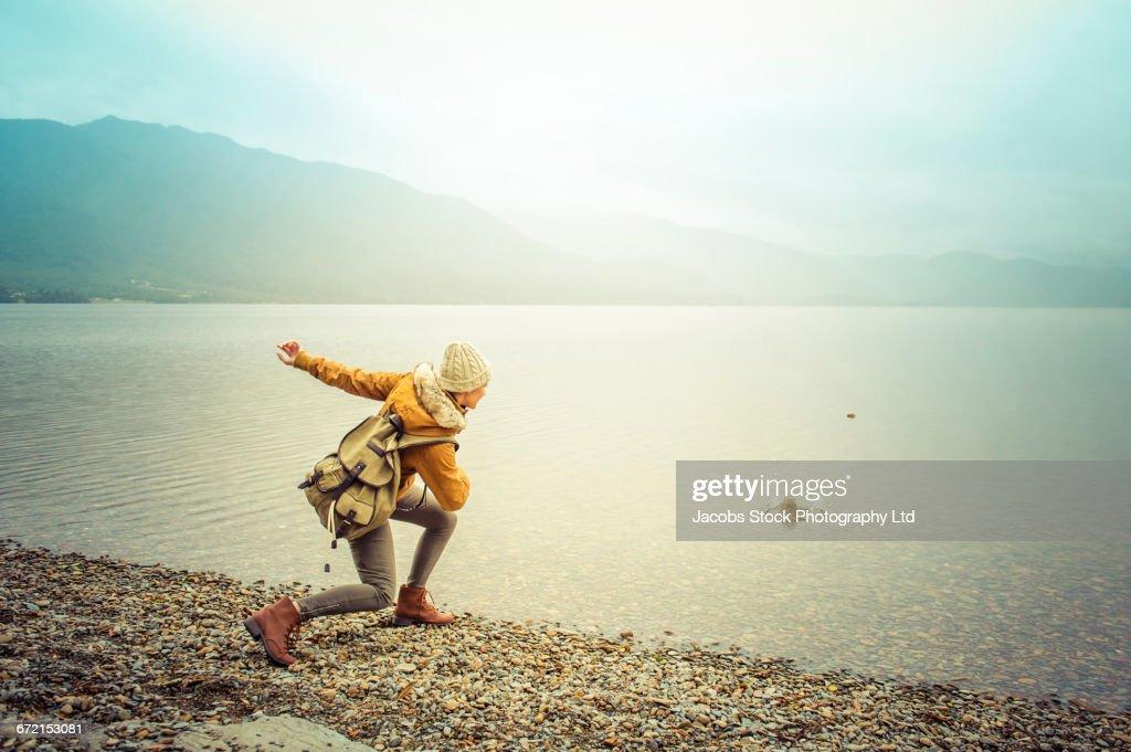 Hispanic woman wearing coat skipping rock at mountain lake : Stock Photo
