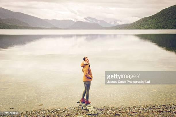 Hispanic woman wearing coat standing on rocks at mountain lake