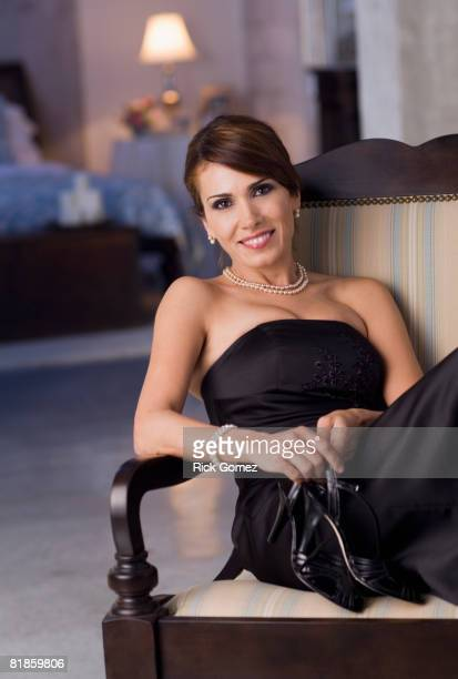 hispanic woman wearing evening dress and holding shoes - strapless evening gown stock pictures, royalty-free photos & images