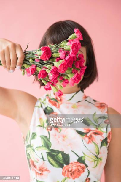 Hispanic woman wearing floral dress holding flowers