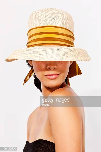 hispanic woman wearing hat to protect from sun - sun hat stock pictures, royalty-free photos & images