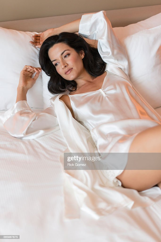 Hispanic woman wearing lingerie in bed : Stock Photo