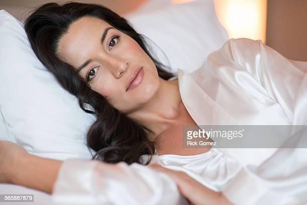 Hispanic woman wearing lingerie in bed