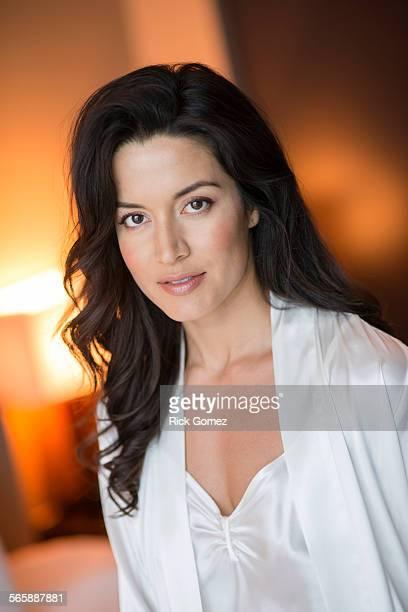 Hispanic woman wearing lingerie in bedroom