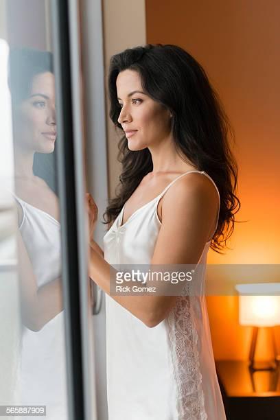 Hispanic woman wearing nightgown at window