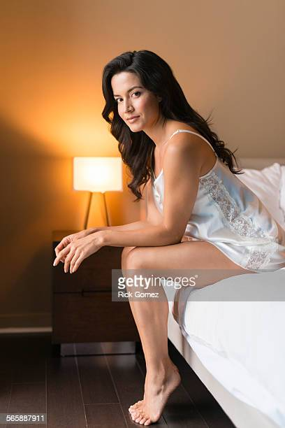 hispanic woman wearing nightgown on bed - women in slips stock photos and pictures