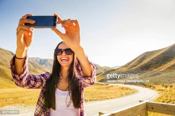 Hispanic woman wearing plaid shirt taking selfie at mountain