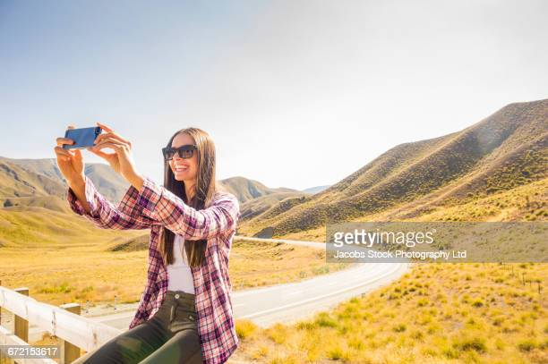 Hispanic woman wearing plaid shirt taking selfie on fence at mountain