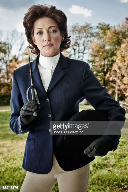hispanic woman wearing riding gear holding hat and crop - riding crop stock photos and pictures