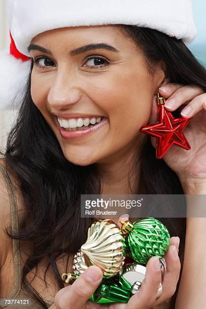 hispanic woman wearing santa hat and holding christmas ornament as earring - santa face stock pictures, royalty-free photos & images
