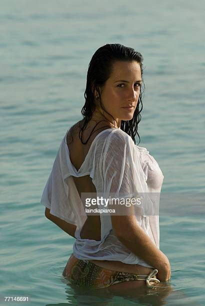 hispanic woman wearing shirt in water - wet t shirts fotografías e imágenes de stock