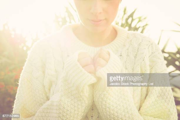Hispanic woman wearing sweater with hands clasped