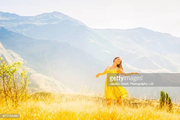 hispanic woman wearing yellow dress dancing in field near mountain - gelbes kleid stock-fotos und bilder