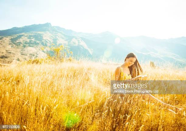 Hispanic woman wearing yellow dress sitting in grass reading book