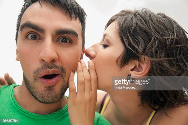 hispanic woman whispering to boyfriend - gossip stock pictures, royalty-free photos & images
