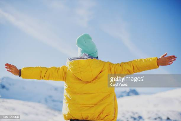 Hispanic woman with arms outstretched in snow:Rear view